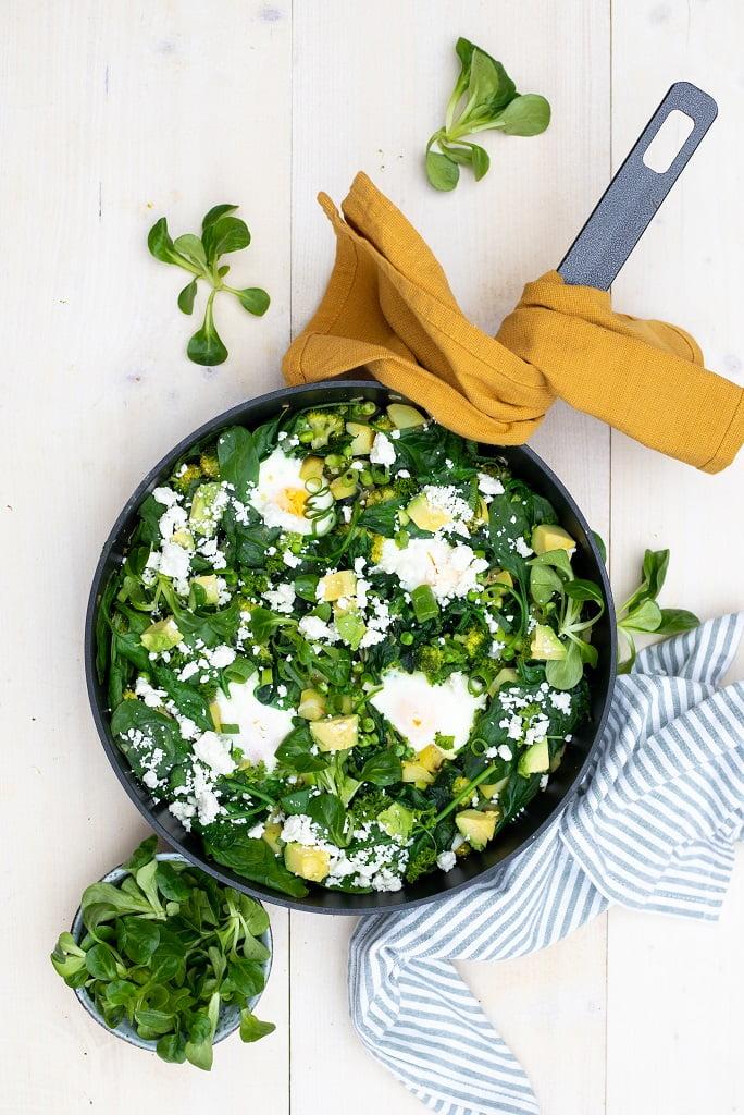 Groene shakshuka in een pan van broccoli, spinazie en doperwten en eieren in kuiltjes