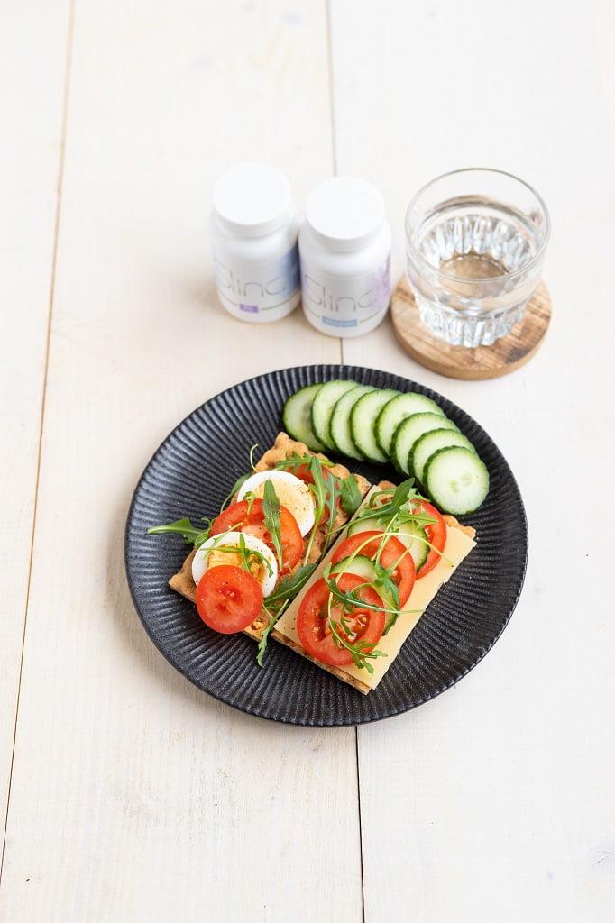 Slinc. lunch met supplementen Slinc. Shaper en Slinc Fit en een glaasje water